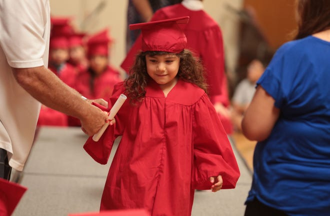 Aaliyah Garcia, 4, gets her diploma during the YMCA La Quinta Child Development Center's preschool graduation on Saturday, June 7, 2014, in Palm Desert.