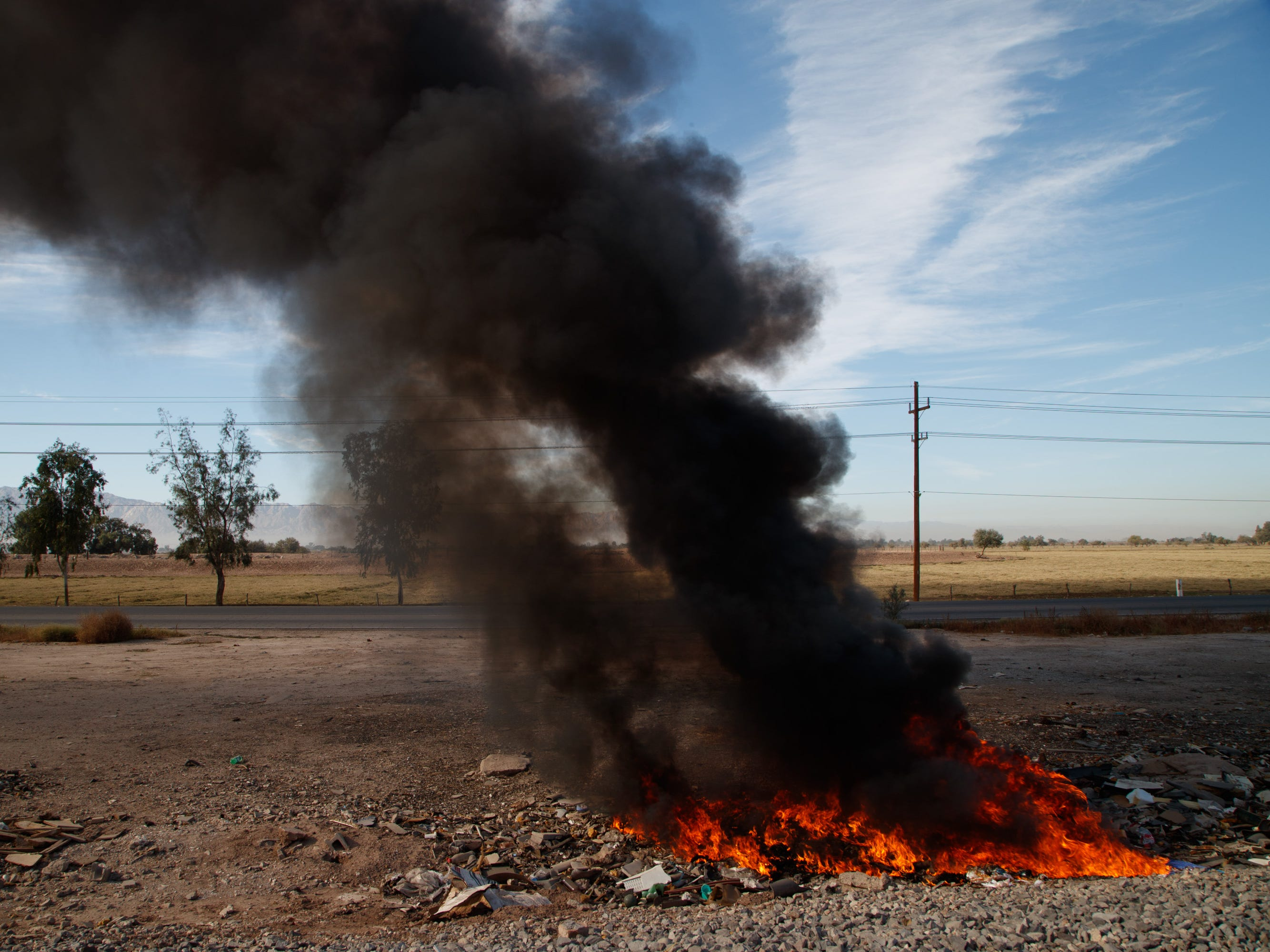 A trash fire releases a thick cloud of black smoke in the countryside on the outskirts of Mexicali, Mexico.