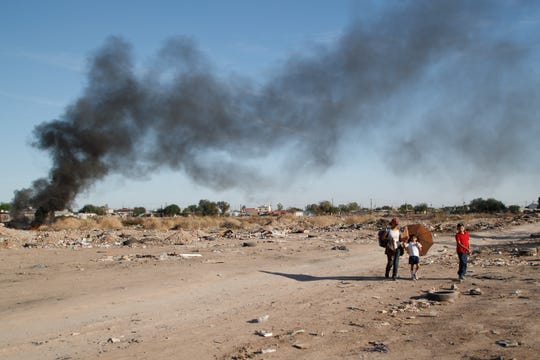 A woman walks two children home from school through a lot where a pile of trash and tires are burning in Mexicali.