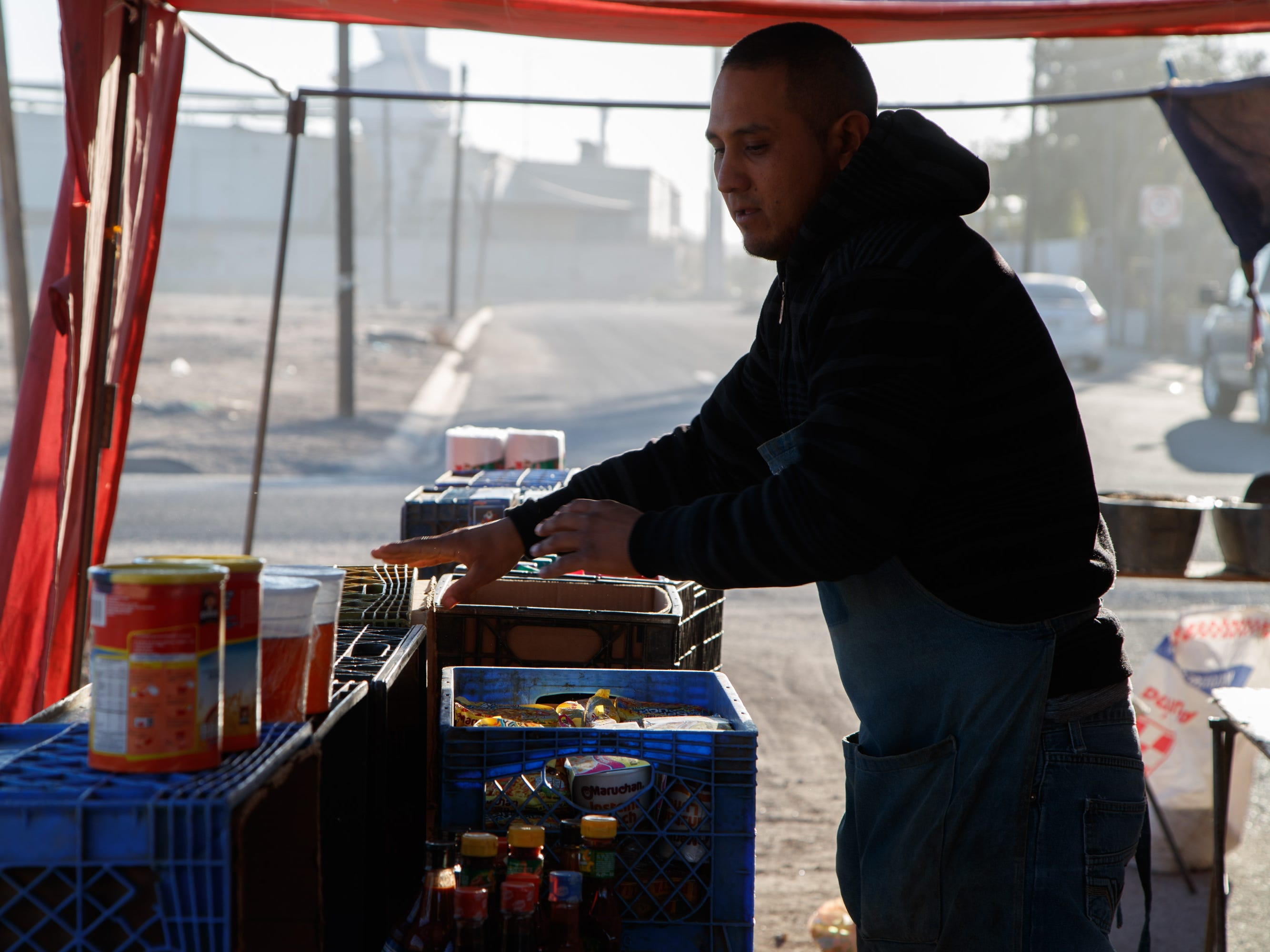 Luis Alberto Rodríguez lays out food at a street market in a Mexicali neighborhood flanked by factories. Behind him is the Smurfit Kappa plant.