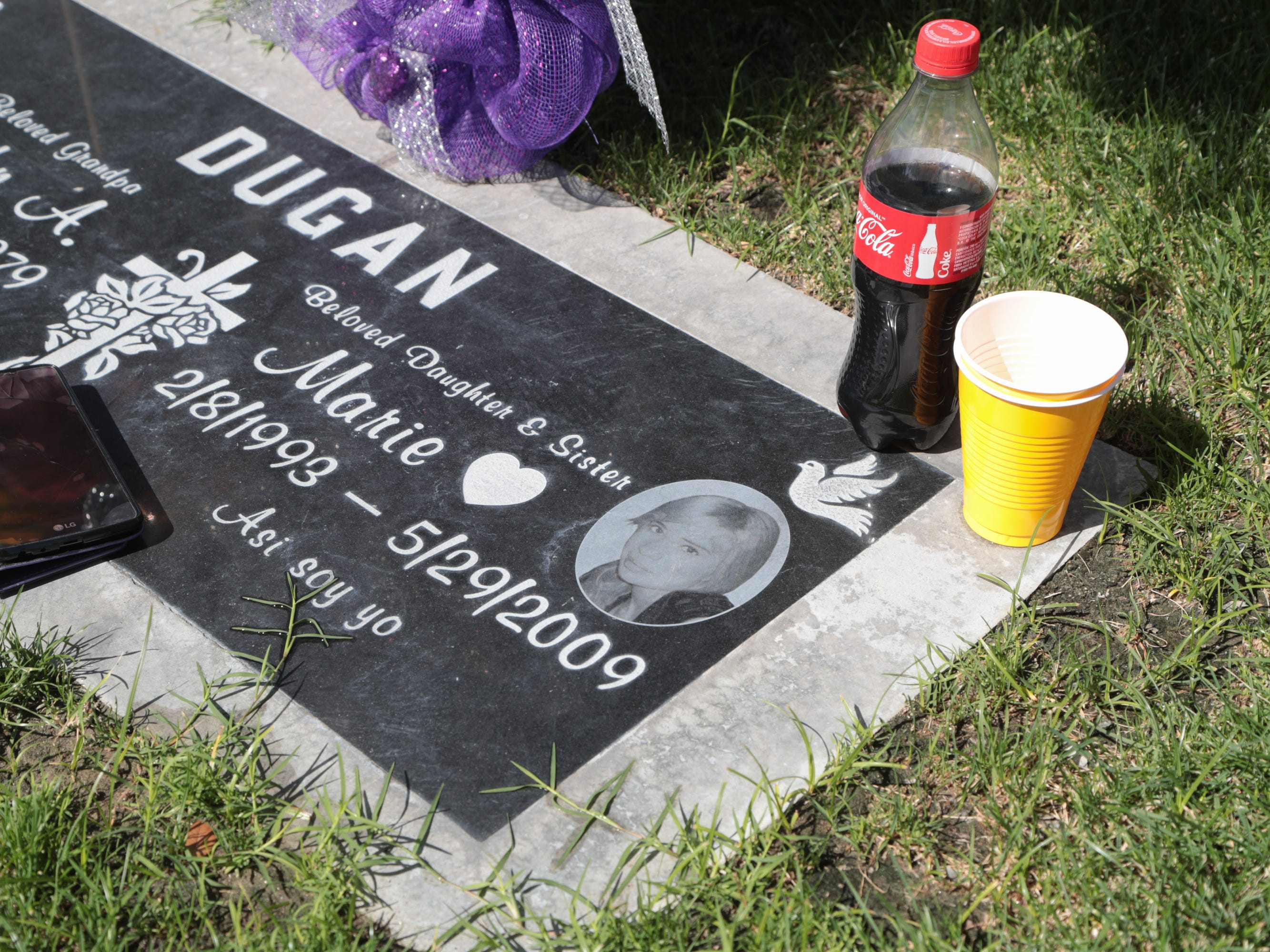 Michelle Dugan-Delgado visits the grave of her sister Marie Dugan at the Coachella Valley Cemetery in Coachella. Marie died of an asthma attack in El Centro in 2009.