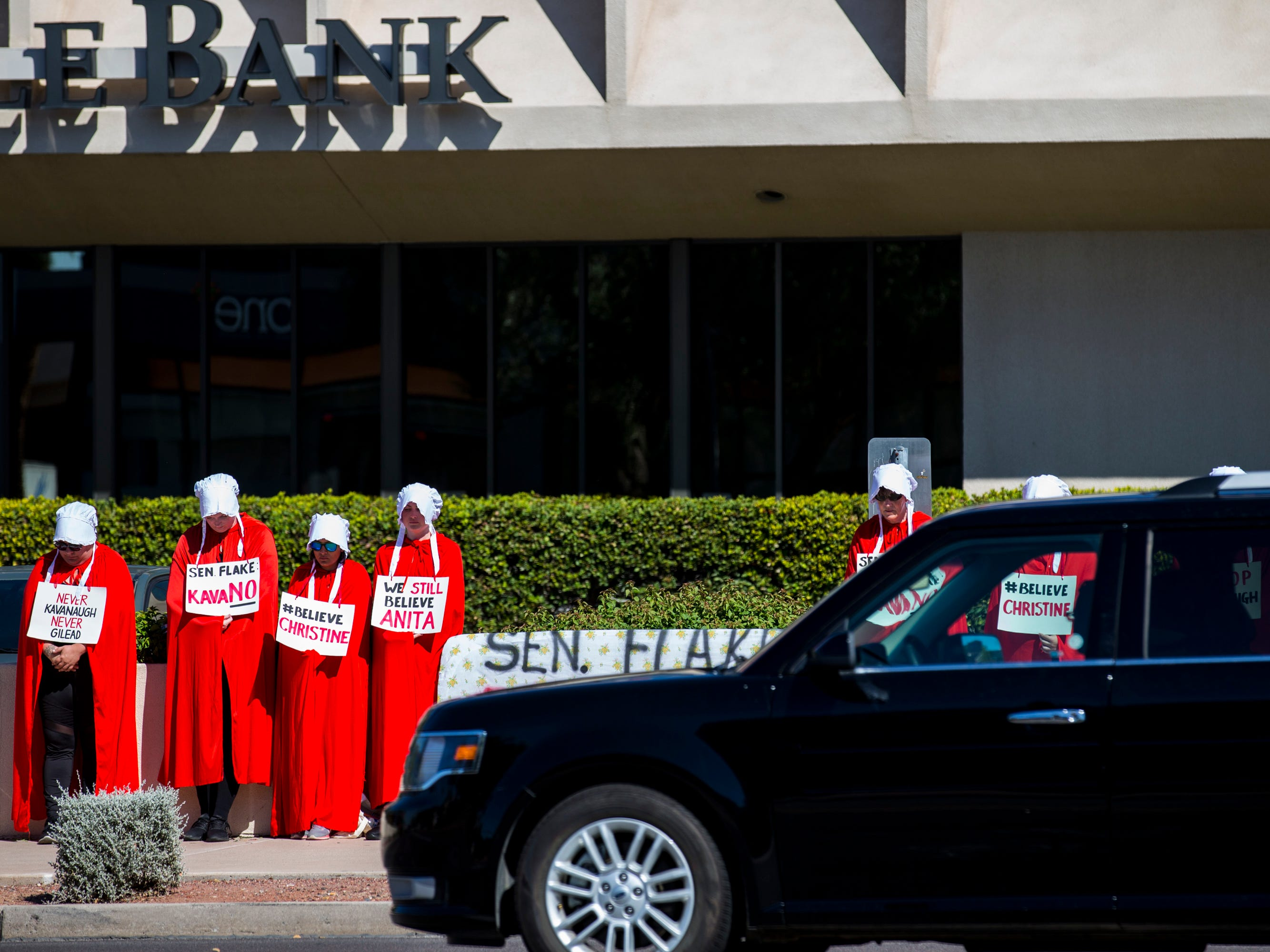 Women dressed as handmaids protest Supreme Court nominee Brett Kavanaugh outside Sen. Jeff Flake's office on Sept. 27, 2018, in Phoenix.