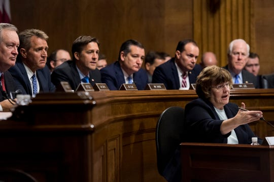 Arizona prosecutor Rachel Mitchell questions Christine Blasey Ford as Senators, from left, Sen. Mike Crapo, R-Idaho; Sen. Jeff Flake, R-Ariz.; Sen. Ben Sasse, R-Neb.; Sen. Ted Cruz, R-Texas; Sen. Mike Lee, R-Utah.; and Sen. John Cornyn, R-Texas, listen during the Senate Judiciary Committee hearing, Sept. 27, 2018 on Capitol Hill in Washington.