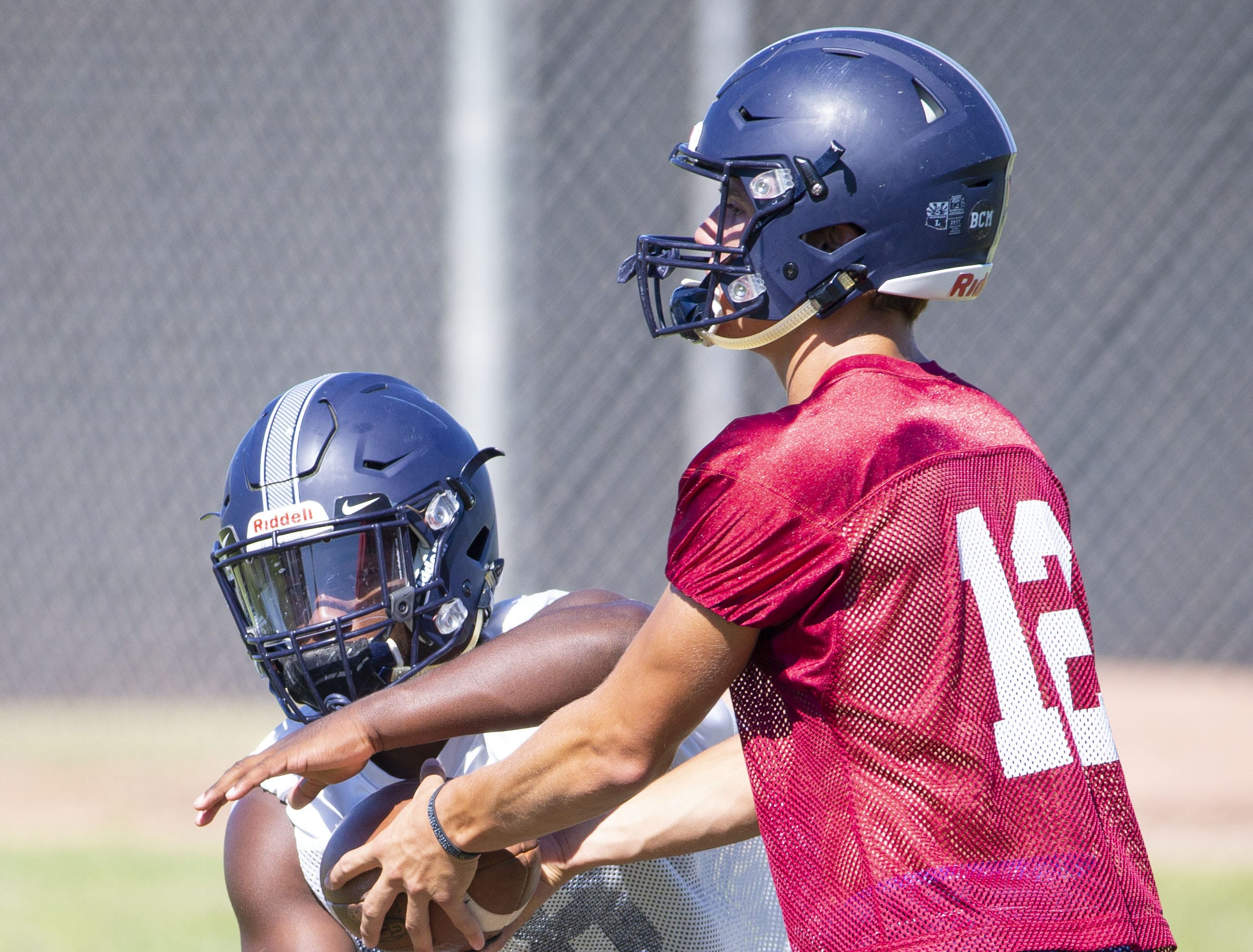 Perry High football quarterback Chubba Purdy, (12) hands off the ball to running back Jalen Young during practice in Gilbert on September 26,  2018.