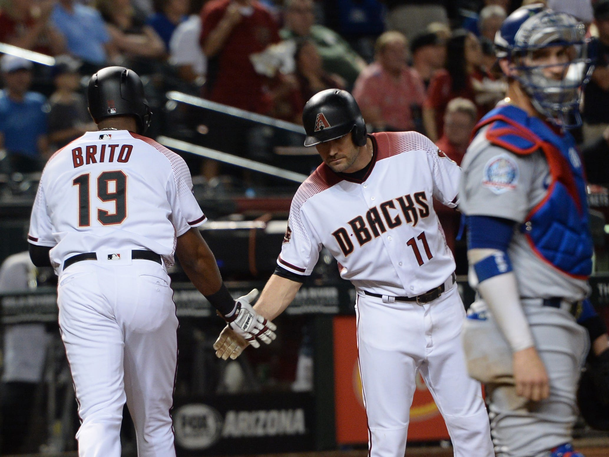 Sep 26, 2018; Phoenix, AZ, USA; Arizona Diamondbacks center fielder Socrates Brito (19) slaps hands with center fielder A.J. Pollock (11) after hitting a solo home run against the Los Angeles Dodgers during the second inning at Chase Field.