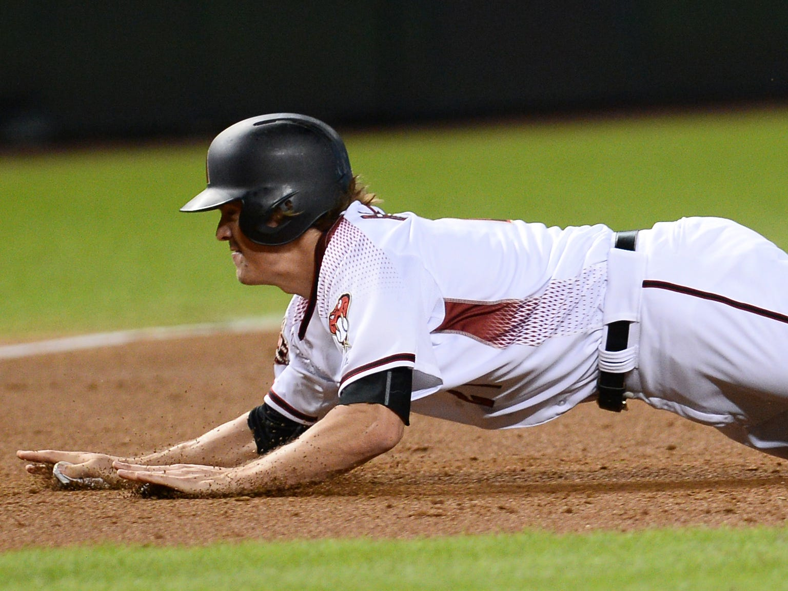 Sep 26, 2018; Phoenix, AZ, USA; Arizona Diamondbacks starting pitcher Zack Greinke (21) dives into third base during a tag up play against the Los Angeles Dodgers during the second inning at Chase Field.