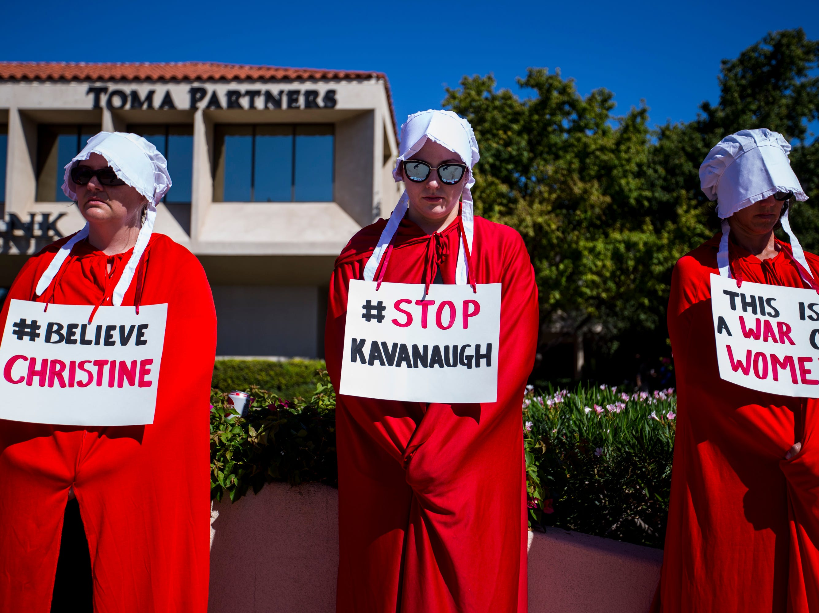 Michele Spiller (from left), Kristin Clark, and Margie Maynard, dressed as a handmaids, protest Supreme Court nominee Brett Kavanaugh outside Sen. Jeff Flake's office on Sept. 27, 2018, in Phoenix.