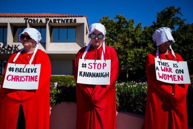 Michele Spiller (from left), Kristin Clark, and Margie Maynard, dressed as a handmaids, protest Supreme Court nominee Brett Kavanaugh outside Sen. Jeff Flake's office on Sept. 27, 2018, in Phoenix.