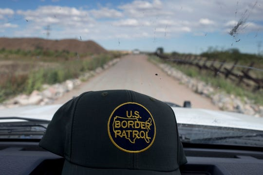 A Border Patrol worker's hat rests atop the dash of a vehicle.