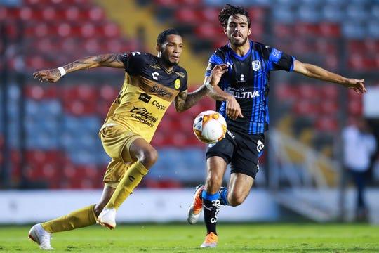 Vinicio Angulo #10 de Dorados de Sinaloa trata de eludir la marca de Victor Milke #5 de Queretaro.