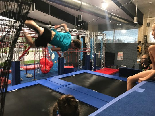 All-American Flames coach Sean Boyd pulls off a stunt at the Fuse Ninja Gym on Lapeer in Port Huron.