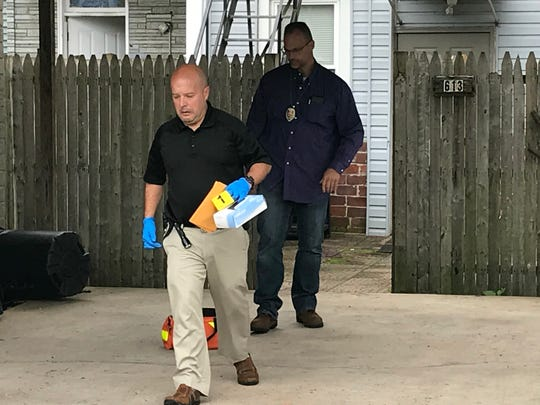 York City Police detectives collect evidence from the scene of two Wednesday night homicides in an alley near the 600 block of West Princess Street.