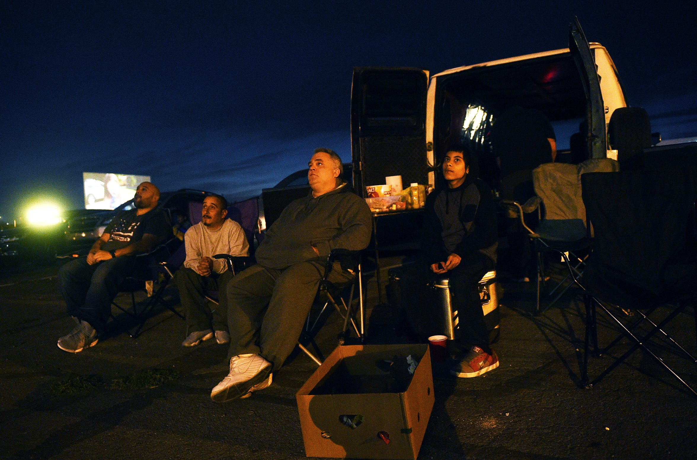 DJ Roney John, right, and Mike Berland, middle, watch the new Predator film with their family at the West Wind El Rancho Drive-In 4 movie theater in Sparks on Sept. 14, 2018.