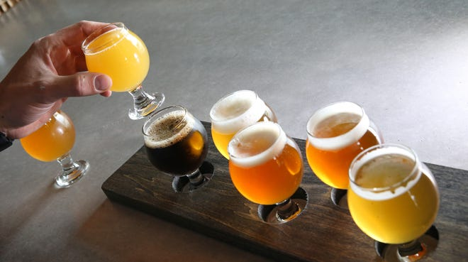 Owner Bill Blake fills a flight of six samplers with a sample of Mango It Was Written Sour IPA at the new Rising Storm Brewing in Livonia Thursday, Sept. 27, 2018.  The samplers are also available in flights of four.