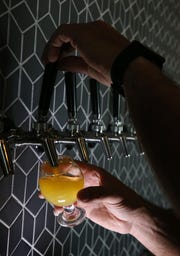 Owner Bill Blake pours a sample of Mango It Was Written Sour IPA at the new Rising Storm Brewing in Livonia Thursday, Sept. 27, 2018.