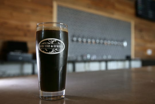 A pint of Stayin' On the Grind Coffee Stout on the bar at the new Rising Storm Brewing.