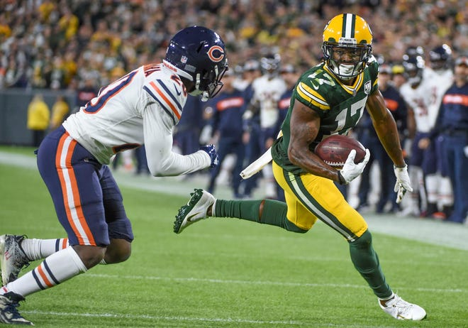 Green Bay Packers wide receiver Davante Adams (17) runs past Chicago Bears cornerback Prince Amukamara (20) after catching a pass for a touchdown in the fourth quarter at Lambeau Field.