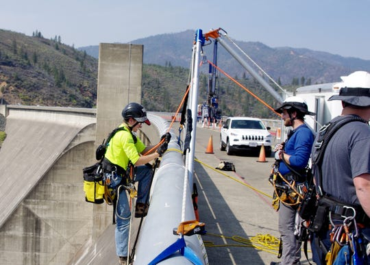 Nathan Morgan climbs back on top of Shasta Dam on Thursday after doing work to prepare for drilling holes in the dam. The holes were being drilled to test the strength of the concrete in preparation for raising the height of the dam.