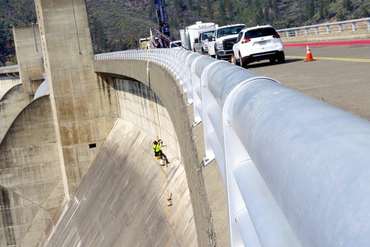 Nathan Morgan hangs over the side of Shasta Dam in September. Morgan and others were drilling holes in the dam to test the strength of the concrete in preparation for raising the height of the dam.