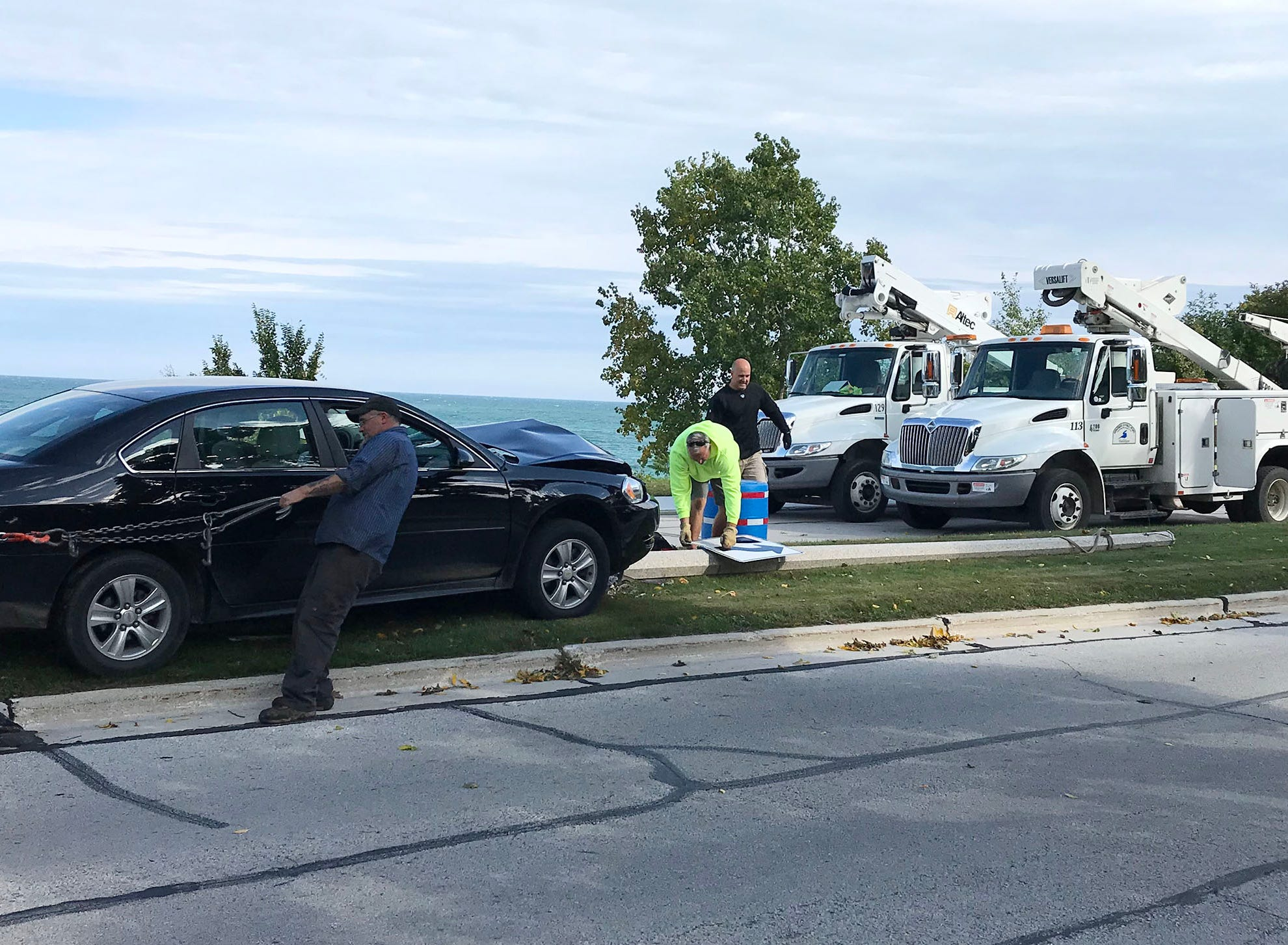 City of Sheboygan Police along with Public Works employees wait for Riteway Towing to remove a vehicle that struck a lamp pole, Thursday, September 27, 2018, in Sheboygan, Wis.