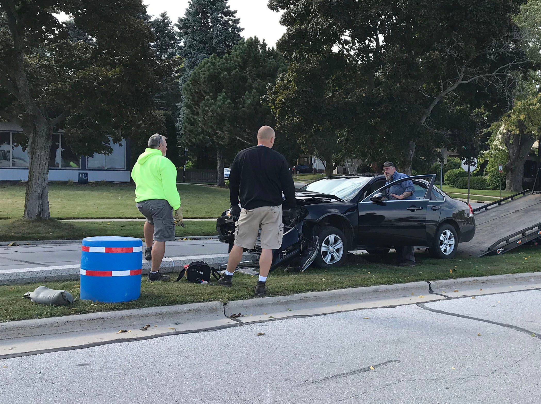 City of Sheboygan Public Works employees wait for Riteway Towing to remove a vehicle that struck a lamp pole, Thursday, September 27, 2018, in Sheboygan, Wis. The