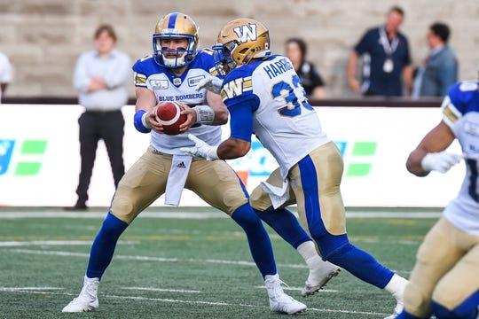 Winnipeg Blue Bombers Quaterback Chris Streveler (17) hands the ball off to Winnipeg Blue Bombers Running back Andrew Harris (33) during the Winnipeg Blue Bombers versus the Montreal Alouettes game on June 22, 2018, at Percival Molson Memorial Stadium in Montreal, QC