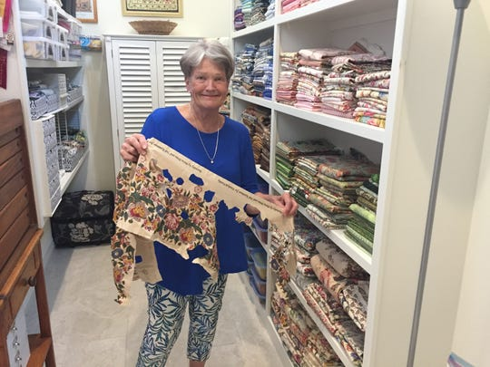 Standing in her fabric pantry, Suzanne Louth grins as she shows off a piece that has been cut up to create her broderie perse designs.