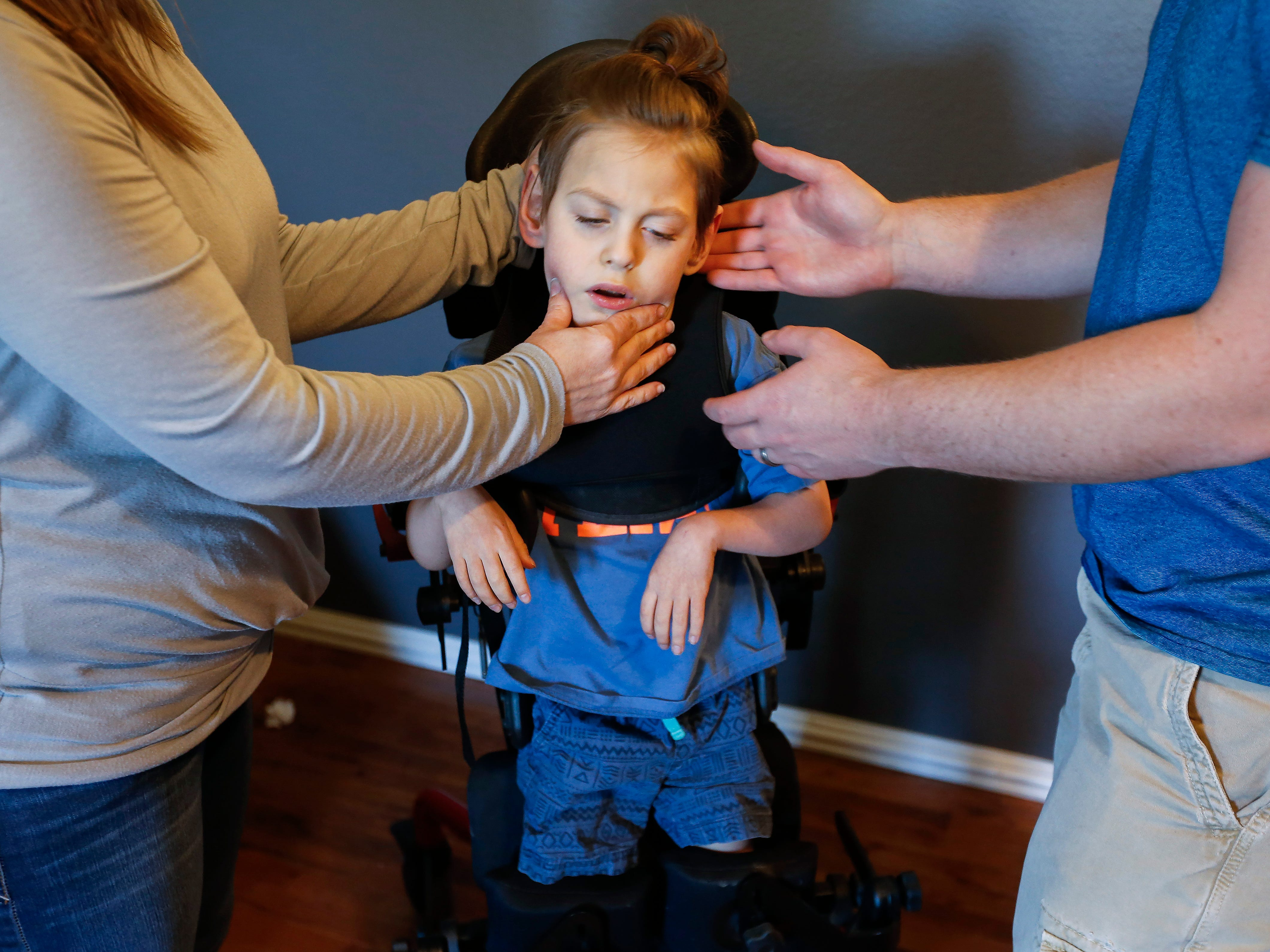 Sara Rozell, a physical therapy assistant, left, and Chris Markum adjust Ayden Markum's head during a therapy session at the Markum's home in Rogersville on Friday, April 27, 2018.