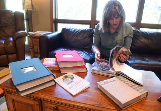 Maria Surma Manka looks through photographs taken during travels with her family during an interview Wednesday, Sept. 26, at her home near Bowlus.