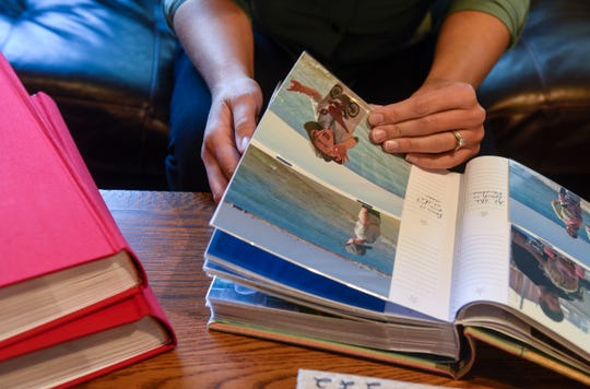 Maria Surma Manka looks through photog albums from her travels as a digital nomad with her family during an interview Wednesday, Sept. 26, at her home near Bowlus.