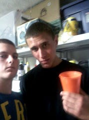 Michael Mandell (left) and Tyler Hadley pose for a picture taken on a cell phone during the party held at Hadley's house after he killed his parents on July 16, 2011.