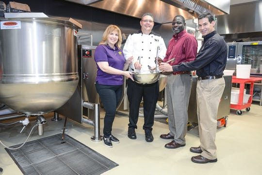 Judy Cruz, left, president and CEO of Treasure Coast Food Bank; with Chef Daniel Leavy, head of the Food Bank's Healthy Harvest Catering Program; Kim Johnson, Food Bank board member, and Geoffrey Sagrans, president and chairman of Localecopia, stand in front of two industrial-sized kettles at Treasure Coast Food Bank's Produce Processing Plant.Here, they mix a bowl of seasonings that will flavor a batch of vegetable soup.