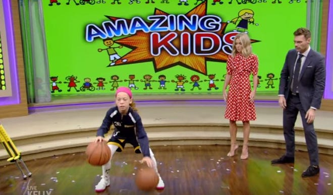 """Karolina Ramirez, 10, of Stuart, shows off her basketball skills Wednesday during """"Live with Kelly and Ryan."""" Hosts Kelly Ripa and Ryan Seacrest look on."""