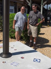 Lee Olsen and architect Tom Staubach show off their flagpole tribute to Waldo's Mountain.