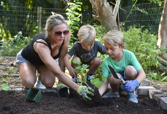 Charlene Wells, teacher for the Treasure Coast District Jr. Master Gardeners, works with home-schoolers, planting vegetables, pumpkin seeds, and peppers in the community garden on Thursday, Sept. 27, 2018, at Heathcote Botanical Gardens in Fort Pierce.