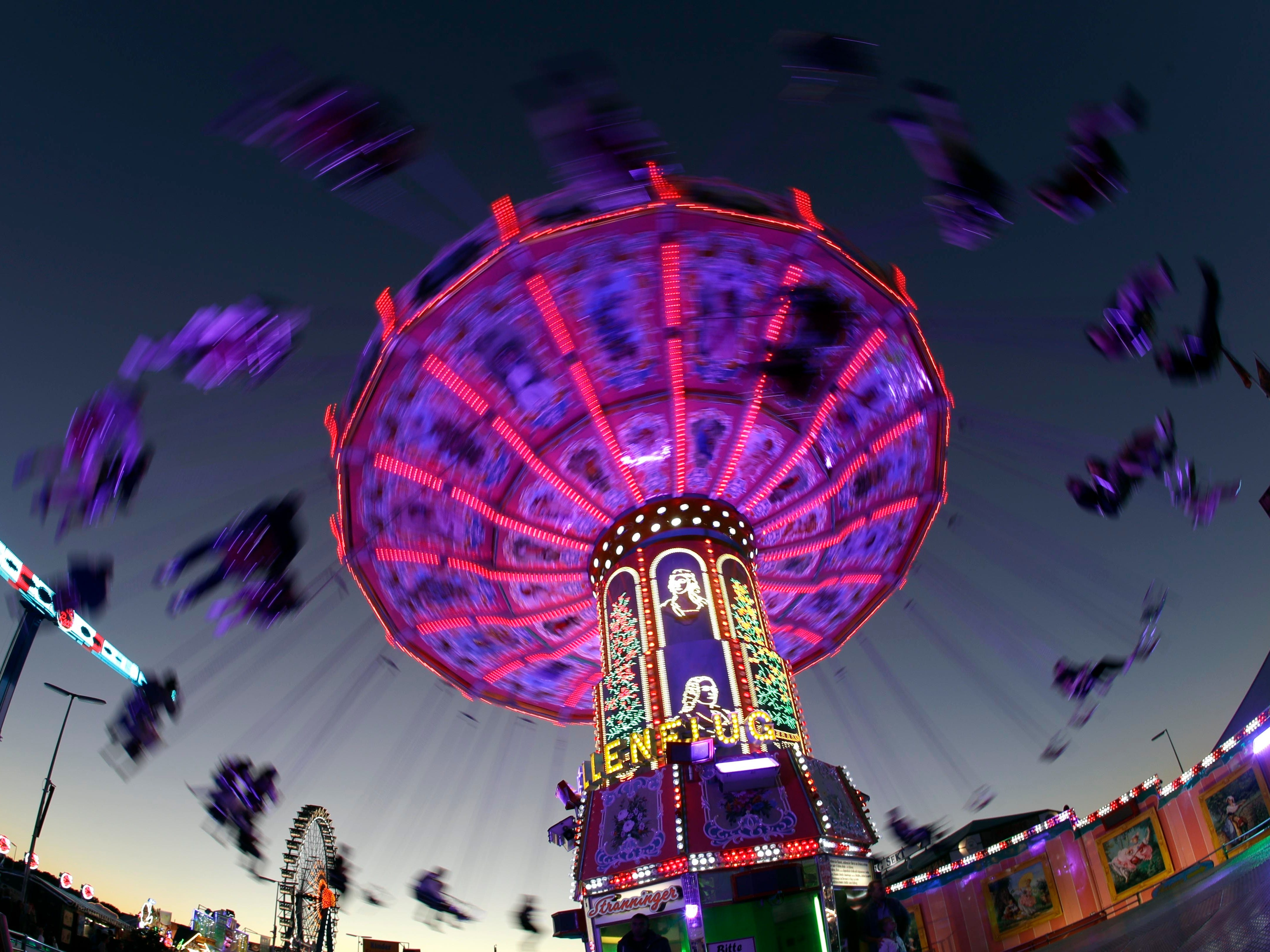 People enjoy a swing ride at the 185th Oktoberfest beer festival in Munich, Germany, Thursday, Sept. 27, 2018.