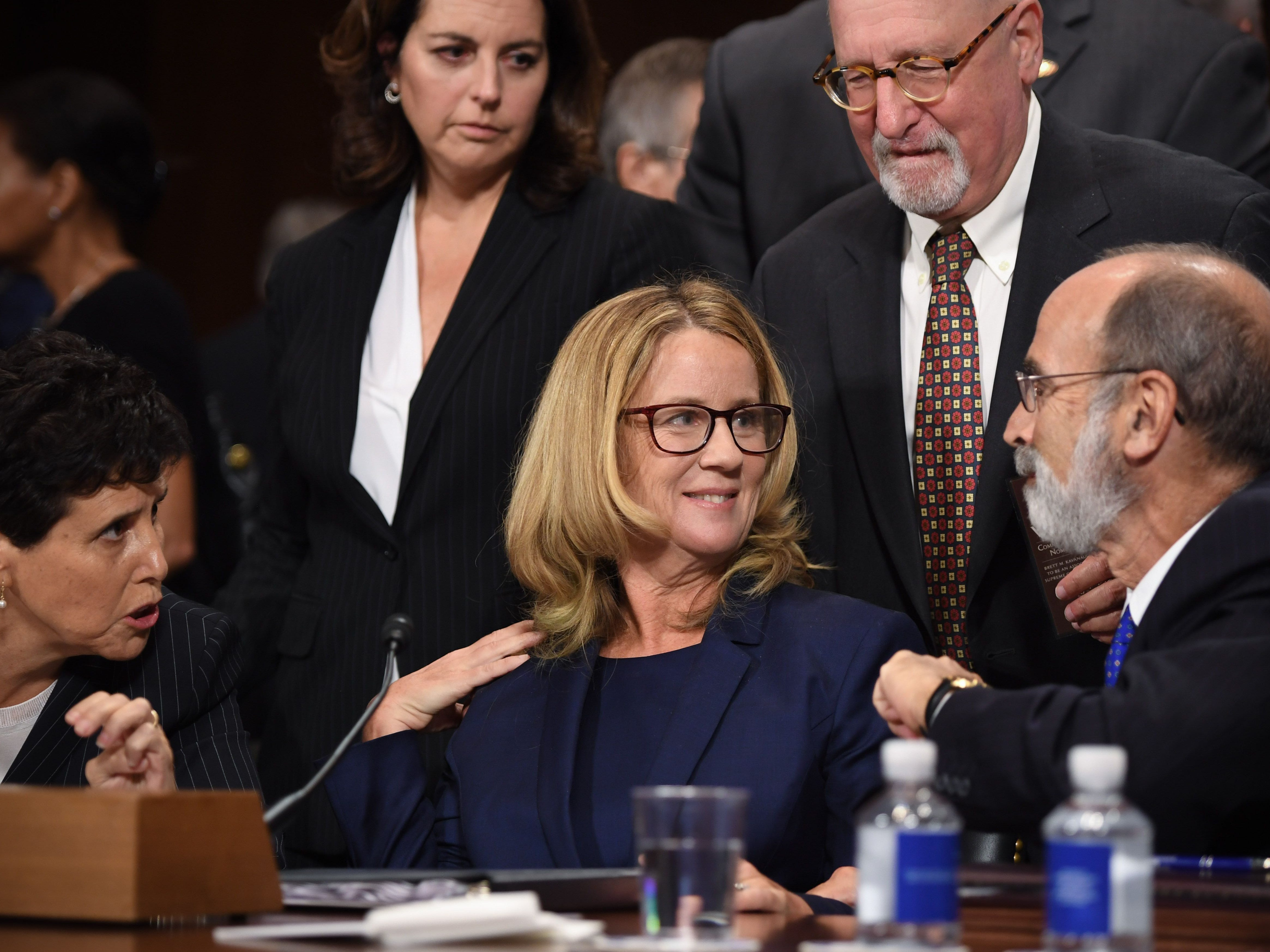 Christine Blasey Ford, the woman accusing Supreme Court nominee Brett Kavanaugh of sexually assaulting her at a party 36 years ago, chats with her attorneys as she testifies before the US Senate Judiciary Committee on Capitol Hill in Washington, DC, September 27, 2018. (Photo by SAUL LOEB / POOL / AFP)SAUL LOEB/AFP/Getty Images ORIG FILE ID: AFP_19I6B6