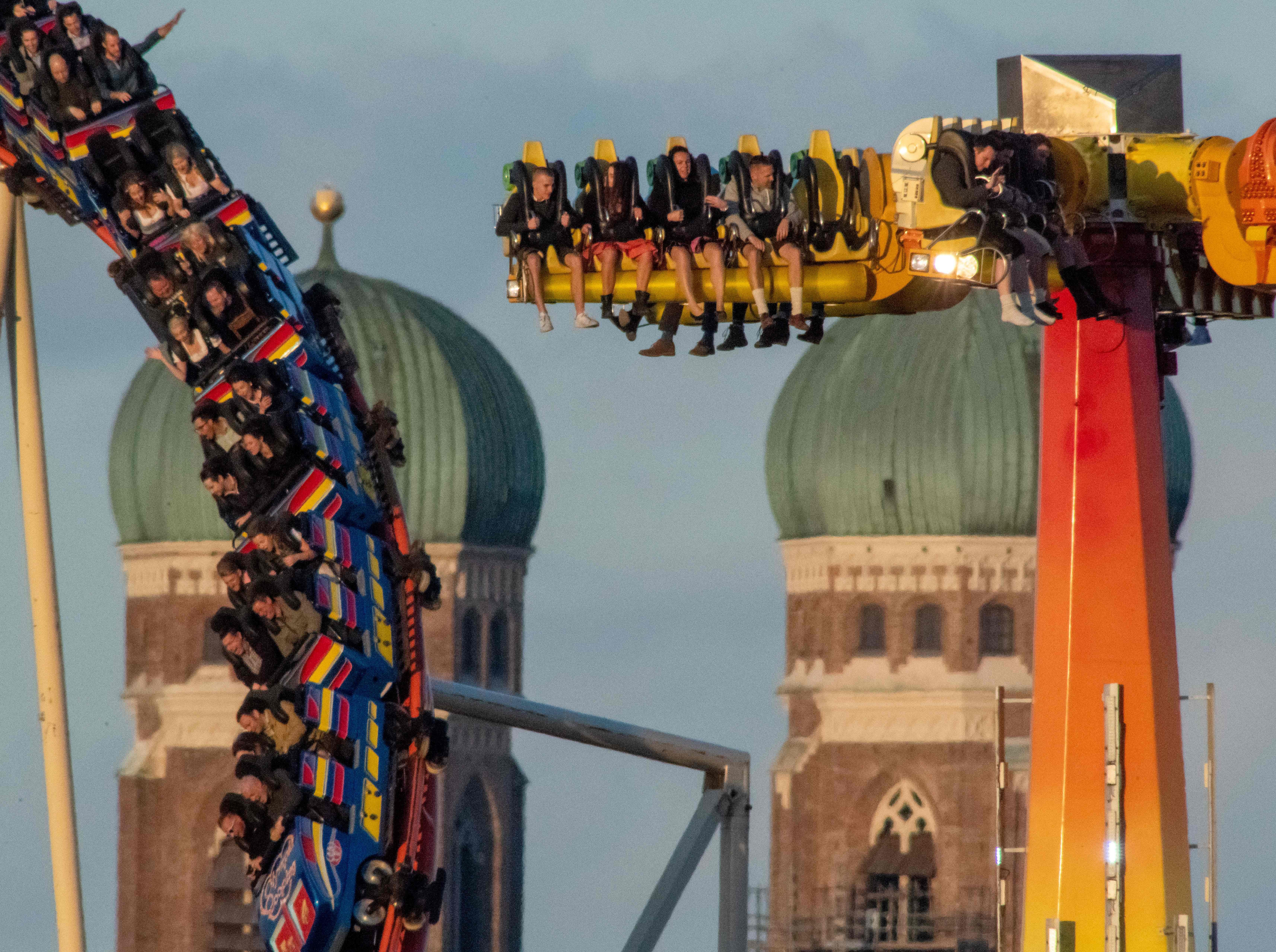 Visitors ride a rollercoaster at the Theresienwiese fair ground with the Frauenkirche (Cathedral of Our Lady) in the background at the Oktoberfest beer festival in Munich, southern Germany, on Sept. 24, 2018.