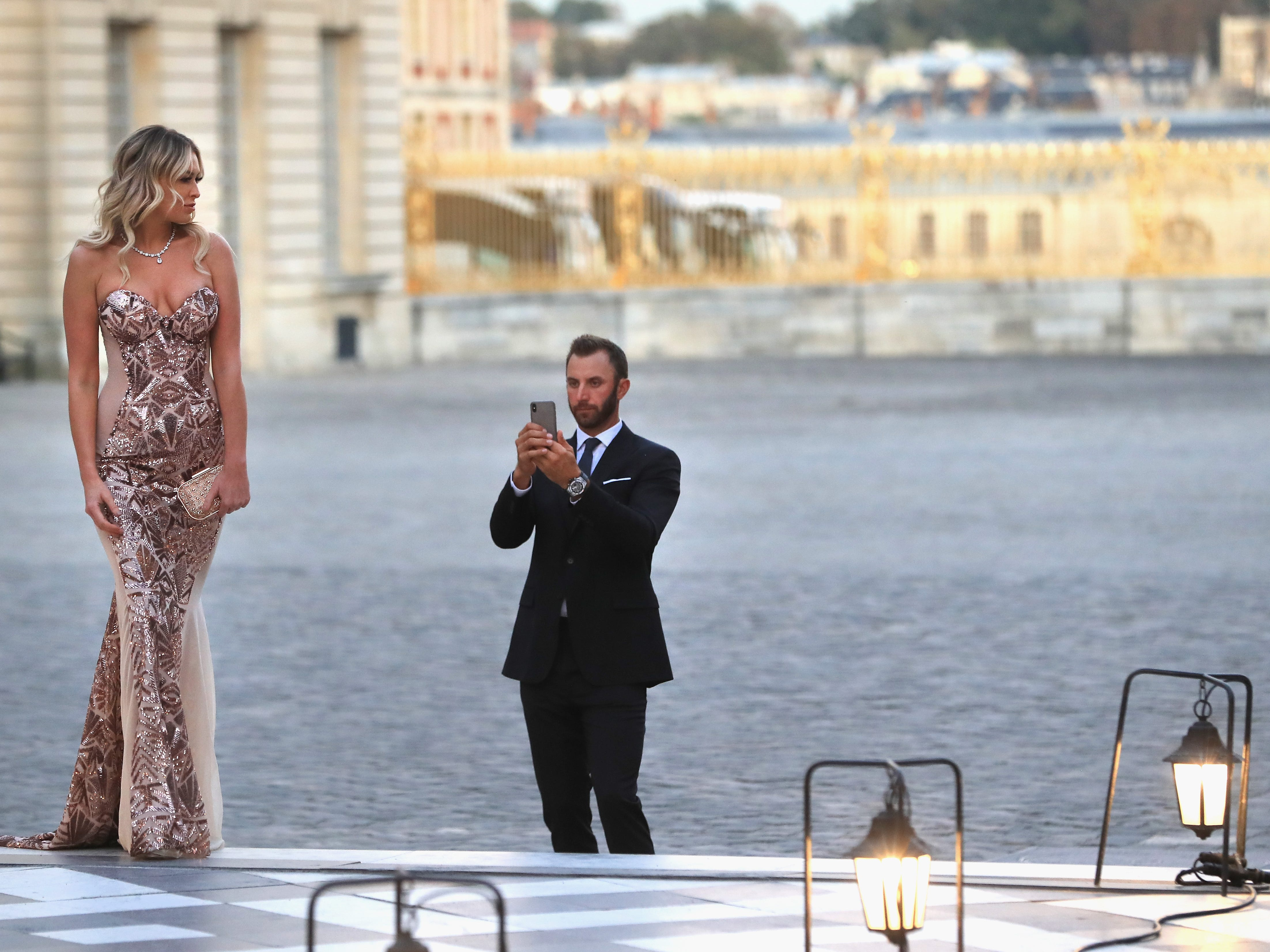 Dustin Johnson takes some shots of his fiancee Paulina Gretzky at the Ryder Cup gala at the Palace of Versailles on Sept. 26.