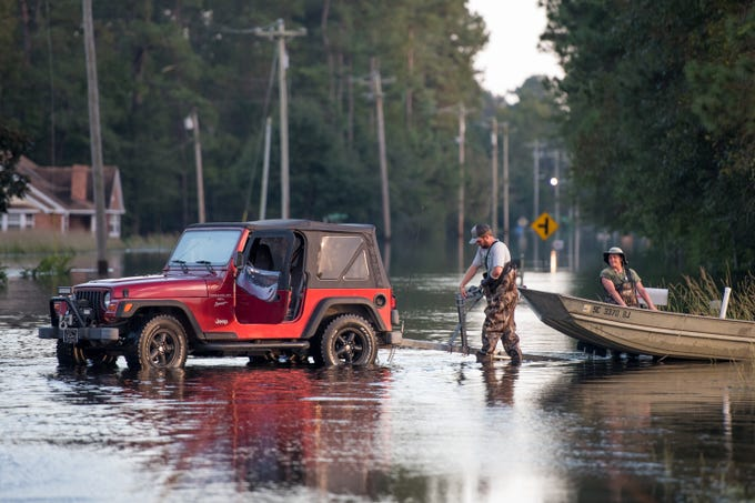 Two people use a neighborhood street as a boat ramp in floodwaters from the Waccamaw River caused by Hurricane Florence on Sept. 26, 2018 in Bucksport, S. C. Nearly two weeks after making landfall in North Carolina, river flooding continues after Florence in northeastern South Carolina.