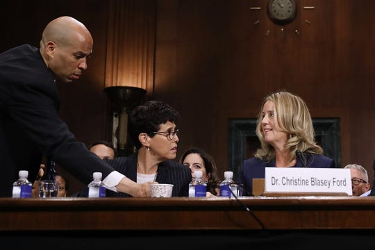 Sen. Cory Booker, D-N.J., left, delivers coffee to Christine Blasey Ford, right, as she testifies before the Senate Judiciary Committee on Sept. 27, 2018, in Washington, D.C.
