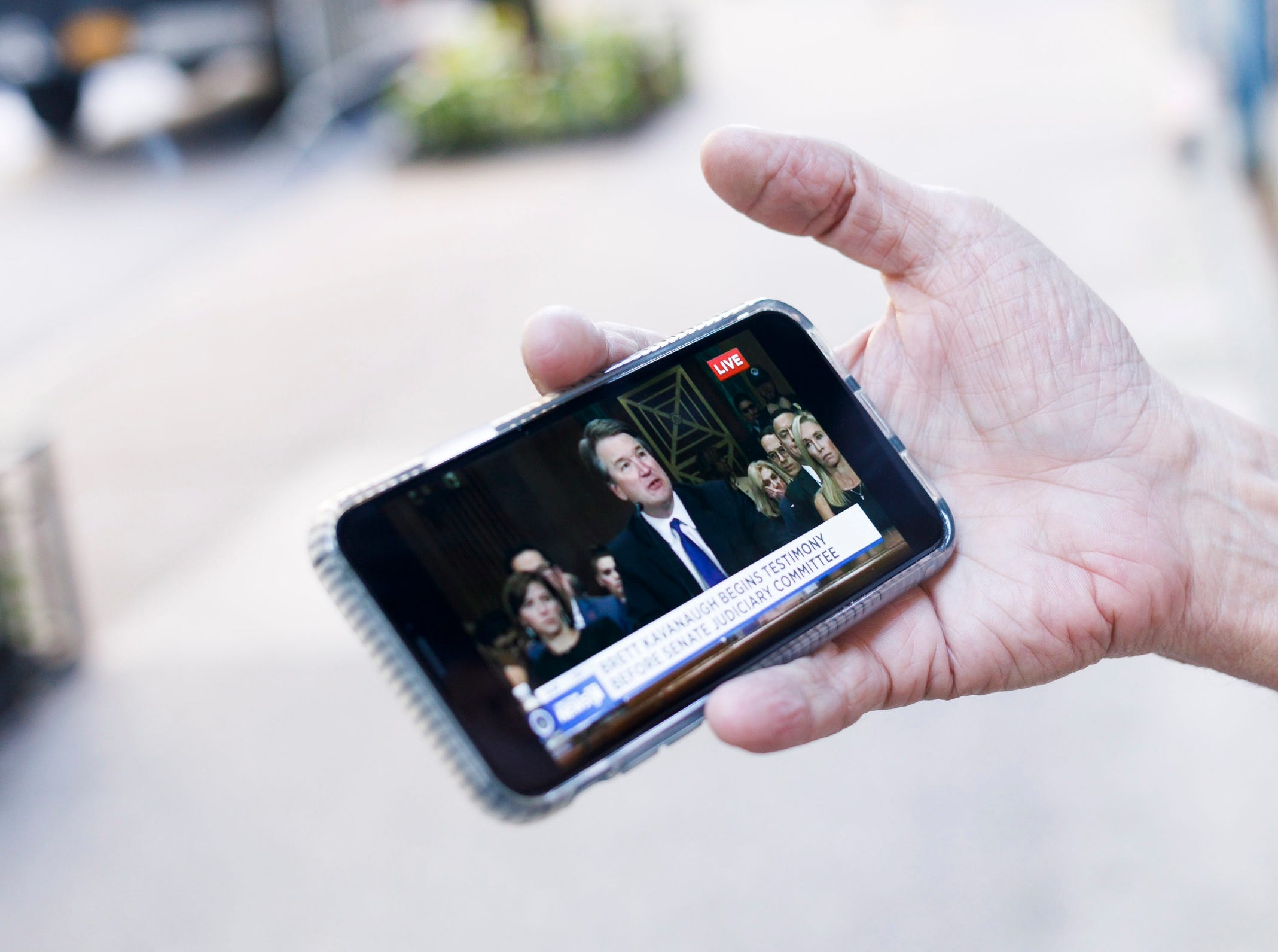 Steven Dupler of New York watches the congressional hearing taking place in Washington DC with Supreme Court nominee Judge Brett Kavanaugh and Christine Blasey Ford, who has accused Kavanaugh of sexual assault, on his phone while standing on the sidewalk in New York.