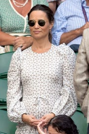 Pippa Middleton wore a printed Anna Mason midi dress with a drop waist, ruffled tiers and a tie around her baby bump when she attended Wimbledon with husband James Matthews on July 13, 2018 in London.