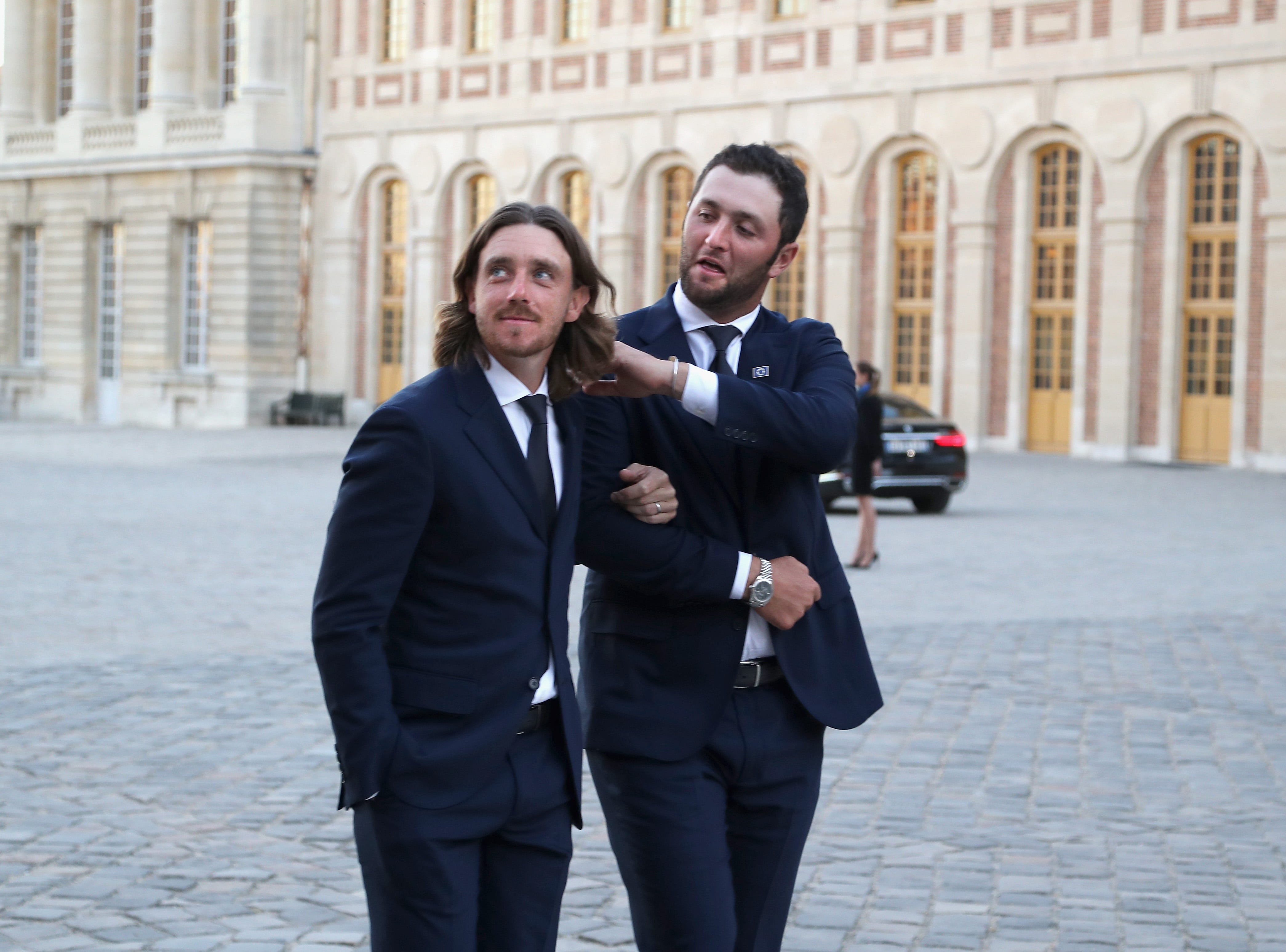 European players Tommy Fleetwood and Jon Rahm walk in arm and arm to the Palace of Versailles for the Ryder Cup gala Sept 26.