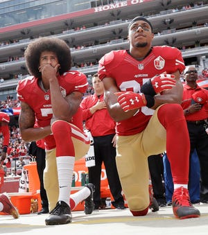 In this Oct. 2, 2016, file photo, San Francisco 49ers quarterback Colin Kaepernick, left, and safety Eric Reid kneel during the national anthem before an NFL football game against the Dallas Cowboys in Santa Clara, Calif.