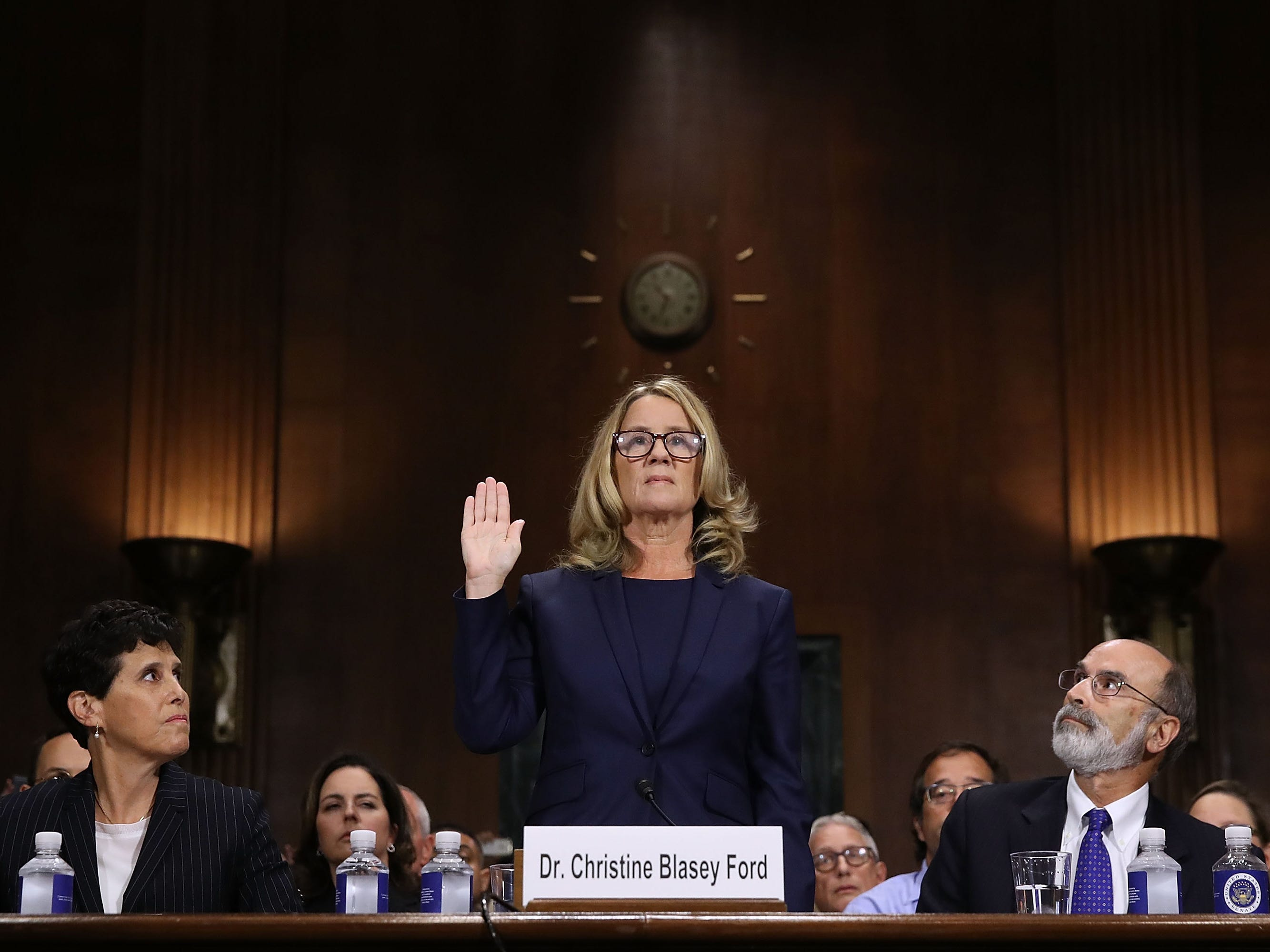 WASHINGTON, DC - SEPTEMBER 27:  Christine Blasey Ford (C) is sworn in before testifying the Senate Judiciary Committee with her attorneys Debra Katz (L) and Michael Bromwich (R) in the Dirksen Senate Office Building on Capitol Hill September 27, 2018 in Washington, DC. A professor at Palo Alto University and a research psychologist at the Stanford University School of Medicine, Ford has accused Supreme Court nominee Judge Brett Kavanaugh of sexually assaulting her during a party in 1982 when they were high school students in suburban Maryland. In prepared remarks, Ford said, ÒI donÕt have all the answers, and I donÕt remember as much as I would like to. But the details about that night that bring me here today are ones I will never forget. They have been seared into my memory and have haunted me episodically as an adult.Ó  (Photo by Win McNamee/Getty Images) ORG XMIT: 775234142 ORIG FILE ID: 1041671342