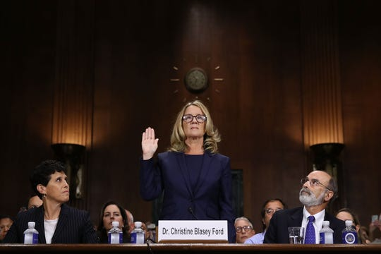 Christine Blasey Ford (C) is sworn in before testifying the Senate Judiciary Committee with her attorneys Debra Katz (L) and Michael Bromwich (R) in the Dirksen Senate Office Building on Capitol Hill September 27, 2018 in Washington, DC.