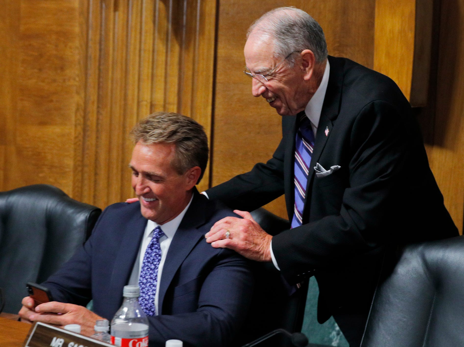 Senate Judiciary Chairman Chuck Grassley (R) speaks with Senator Jeff Flake (L) during a break during the Senate Judiciary Committee hearing on the nomination of Brett Kavanaugh to be an associate justice of the Supreme Court.