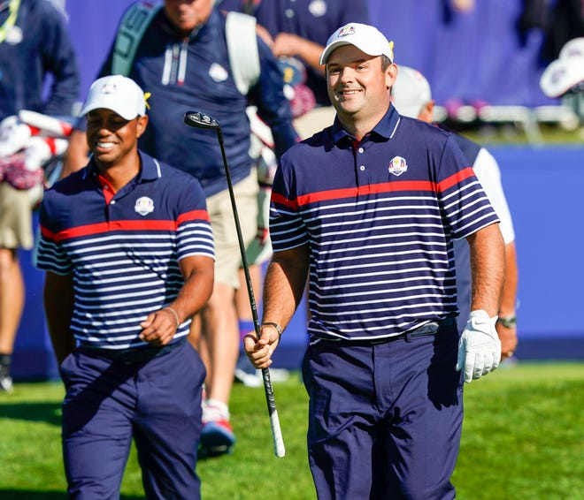 Tiger Woods and Patrick Reed smile as they walk from the 1st tee during a Ryder Cup practice round at Le Golf National.