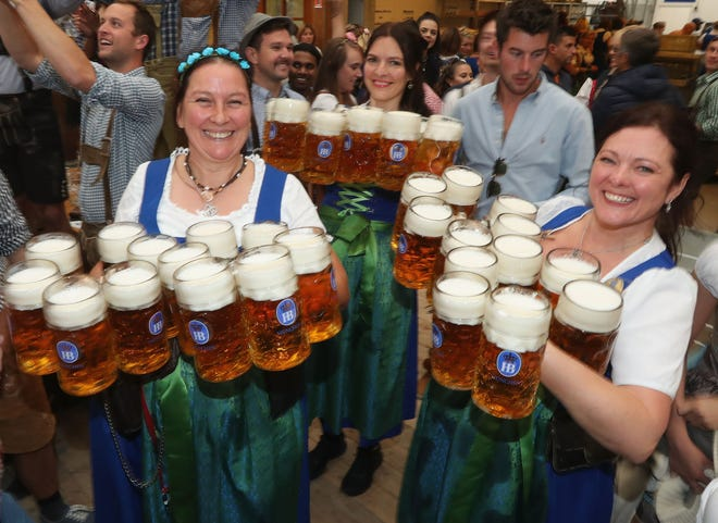 Waitresses carry beer steins in a beer tent on the opening day of the 2018 Oktoberfest on Sept. 22, 2018, in Munich, Germany.